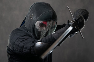 A man in a scary mask with a beard with a skid swords. Historical European Martial Arts, armor and weapons for practice. With a two-handed sword. gray background studio shooting.