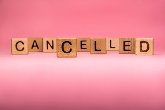 CANCELLED word made with building blocks, business concept. Word CANCELLED on pink background. Global mass gathering cancelled. Cancelled background, Plan changing.