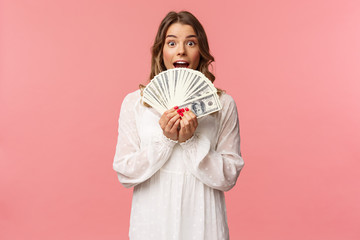 Portrait of excited lucky girl with blond hair, white dress, winning money, receive cash award, big lottery prize, holding dollars near face, smiling and looking amazed, standing pink background