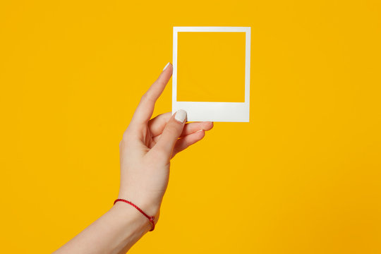 female hand holds empty instant photo frame isolated on yellow background