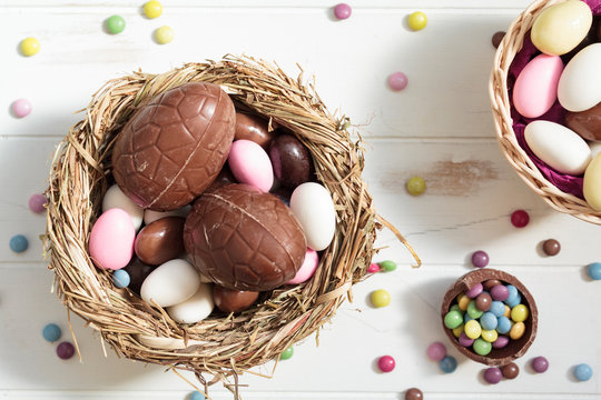 Top view of bird nest with chocolate eggs and easter almonds and sweets on white wooden table