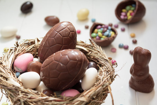 Delicious Chocolate eggs and easter almonds on nest, chocolate bunny and sweets on white wooden table