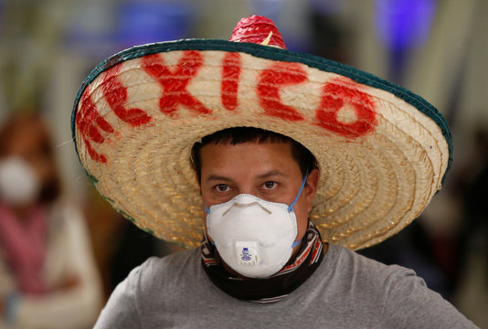 A stranded Ecuadorian tourist, wearing a face mask and a traditional Mexican hat, is pictured while waiting for a new flight after Ecuador's government closed its borders due to the spread of the coronavirus disease (COVID-19), at the Benito Juarez Interna