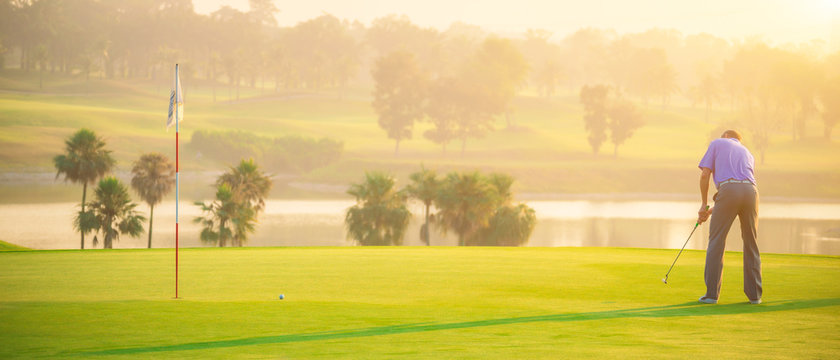 Golfers putting golf balls on the green amid the warm sunshine in the morning. Concept of Outdoor activities and Outdoor sports, Concept of Golfer and Lifestyle.