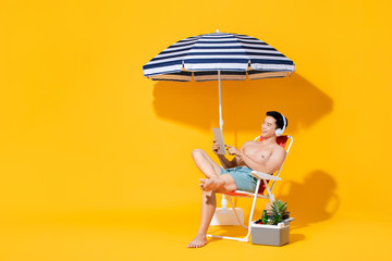 Portrait of young shirtless Asian man sitting on beach chair relaxing and listening to music in isolated summer yellow background