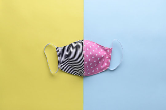 colorful pink and black fashion face mask handmade from fabric cloth on blue and yellow background