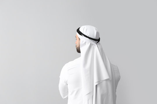 Handsome Arab man on grey background, back view