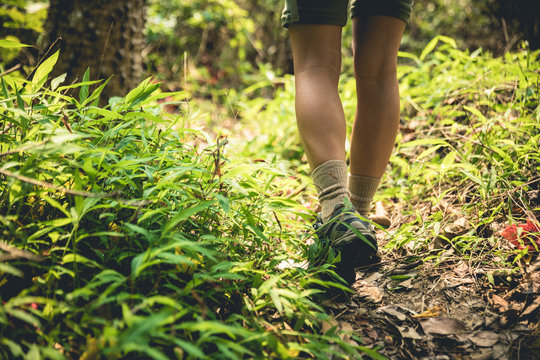 Young woman hiker legs walking on trail in spring mountains