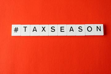 Letter tiles spelling tax season on red backgound