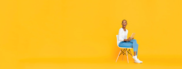 Trendy smiling African American woman sitting on a chair using tablet computer thinking and looking at empty space aside isolated yellow banner background