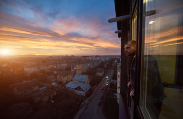 Side view of a smiling man looking away from a balcony at sunset. Beautiful city landscape of a...