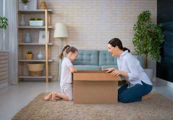 Mother and daughter unpacking box