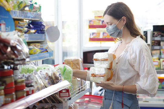 Woman wearing protective mask while grocery shopping in supermarket, Coronavirus contagion fears concept