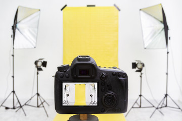Camera in a photo studio with yellow backdrop and light equipment