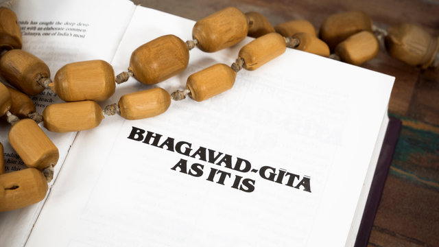 Opened Bhagavad Gita and rosary lying on a wooden table.