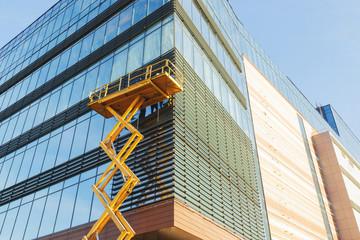 Russia, Nizhny Novgorod, November 2019: Builders on the air platform during installation of facade glazing. The scissor lift platform ensures safe operation at height.
