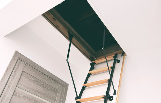 Wooden staircase to the attic in the house