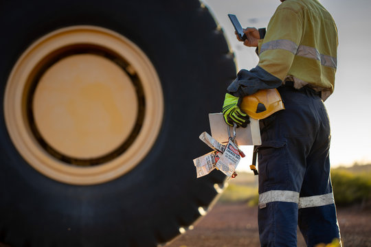 Haul truck driver wearing work uniform safety glove holding hard hat danger tags personal locks and inspection pre operation book taking pic with cell phone  background defocused haul truck background