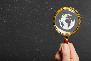 Wall Mural - man holds a magnifier on a earth