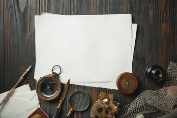 Old fashioned flat lay with letters writing accessories on dark wooden background. White sheets, pen, signet, package, ink. Vintage style, steampunk, gaslight concept. Magnifying glass and compass. Wall mural