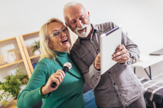 Senior couple singing karaoke at home, having fun.Quarantine.