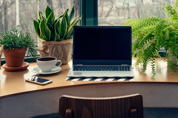 Poster Vegetal Design office desk with green plants and laptop with mock up in vintage style. Workspace with window in modern interior. Technology, business with smartphone and computer in cafe.