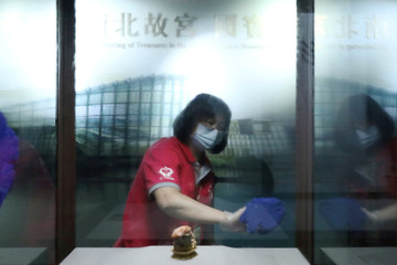 A staff cleans and disinfects a display window to protect the guest from the coronavirus disease (COVID-19) at the National Palace Museum in Taipei