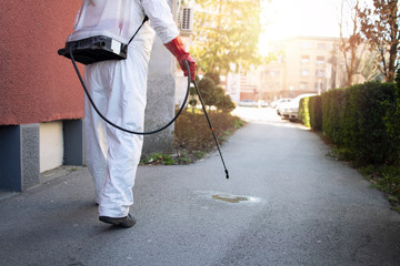 Disinfection corona virus. Unrecognizable person in white protective hazmat suit walking through city streets and spraying disinfectant to stop spreading highly contagious coronavirus or COVID-19.
