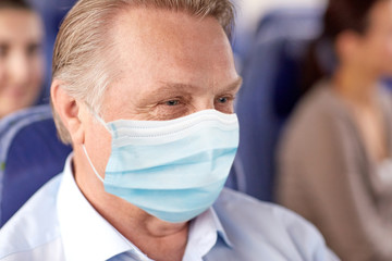 transport, tourism and pandemic concept - close up of senior male passenger wearing protective medical mask for protection from virus sitting in travel bus or airplane