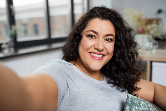 people, technology and leisure concept - happy smiling young woman taking selfie at home