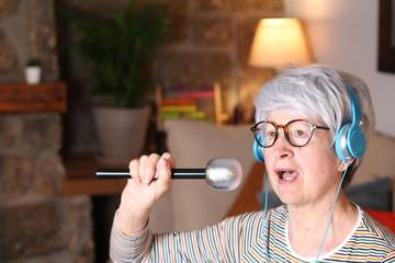 Elder lady singing karaoke at home  Fotobehang