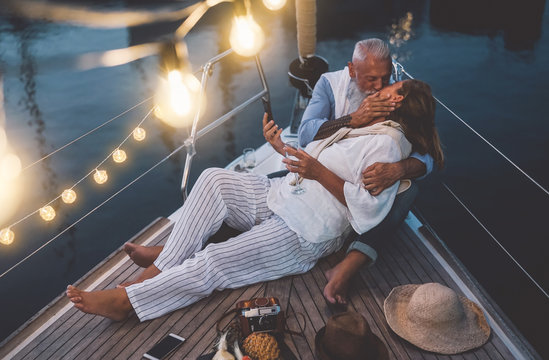 Senior couple kissing during sailboat vacation - Happy mature people having tender moments celebrating wedding anniversary on boat trip - Love relationship and travel lifestyle concept