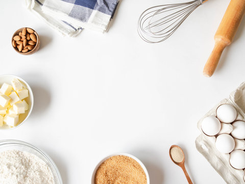 Frame of various baking ingredients - flour, eggs, sugar, butter, dry yeast, nuts and kitchen utensils on white background. Top view.