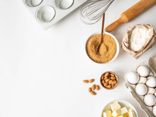 Set of various baking ingredients - flour, eggs, sugar, butter, nuts, kitchen utensils and cupcake baking dish on white background. Top view.
