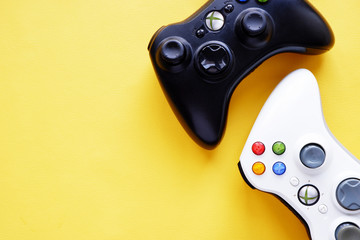 Kharkiv, Ukraine-March 17, 2020: two joysticks for XBox on a yellow background. Game concept
