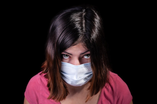 black-haired girl with green eyes donned a white medical face mask from a coronavirus pandemic disease infection COVID-19 isolated on black background.