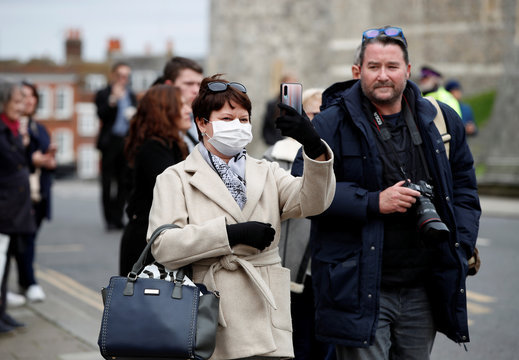 A woman wearing a face mask takes a photograph as the number of coronavirus cases grow around the world