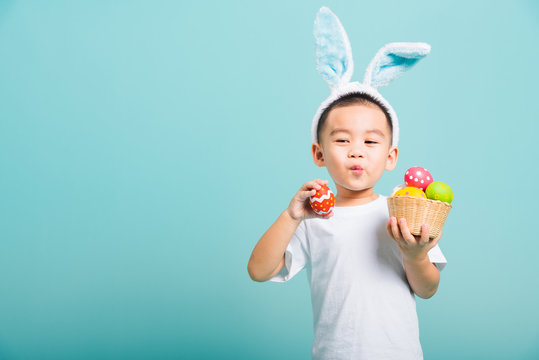 little child boy smile wearing bunny ears and white T-shirt, hold basket with full Easter eggs