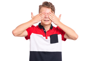 Poster - See no evil concept. Portrait of smiling teen boy with hands on face covering eyes for surprise. Positive beautiful teenager close eyes with palms. Happy caucasian child isolated on white background.