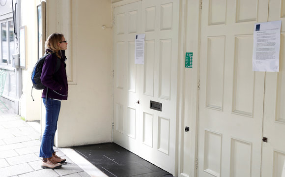 A woman looks at a message on a door at the Theatre Royal as the number of coronavirus cases grow around the world