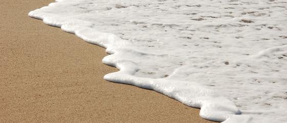 Bannière d'une douce vague blanche pleine d'écume sur le sable d'une plage de sable fin Fototapete