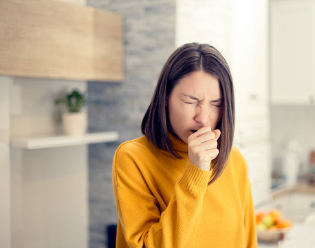 Ill woman with flu virus caughing sneezing indoors at home