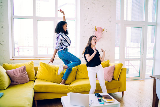 Cheerful teenager dancing in living room