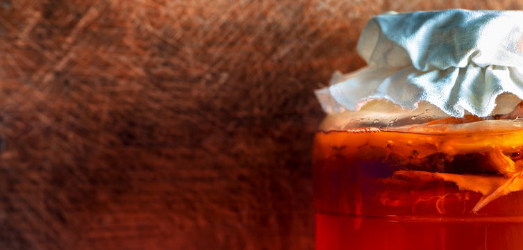 Kombucha tea fermentation process in big glass jar, close-up. Kombucha jar with scoby - mushroom and wooden rustic background. Copy space for text.