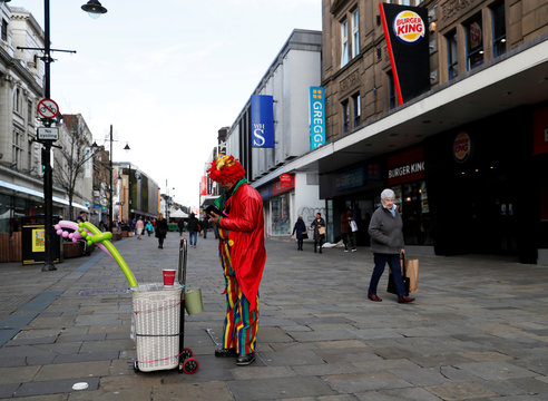 A performer as a woman looks on in a street in Newcastle as coronavirus cases grow around the world