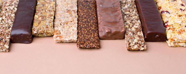 Different Energy protein bars and oatmeal bars on light brown chocolate background. Set of energy, sport, breakfast and protein bars. Copy space. Banner
