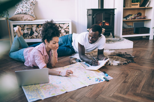 Modern diverse couple planning trip at home