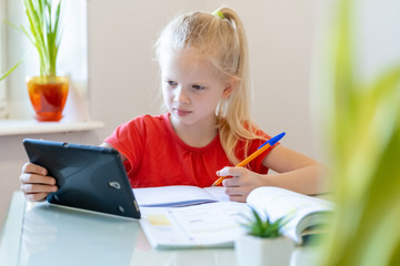 Distance learning online education. Schoolgirl studying at home with digital tablet and doing school homework. Training books and notebooks on table