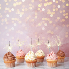 Birthday cupcakes with sparklers on table against light pink background