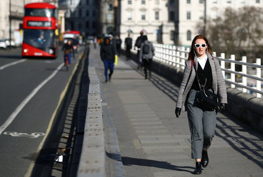 A woman walks across Waterloo Bridge during rush hour, as the number of Coronavirus cases grow around the world, in London